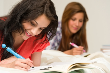 Young teenage girls lying and studying on bed Stock Photo - 20244513