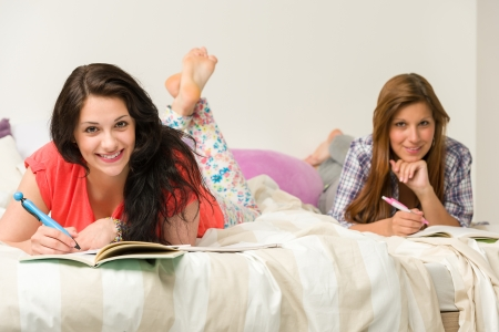 dorm: Young cheerful girls learning and smiling at camera