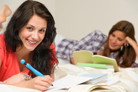 college dorm: Smiling happy female students preparing for exam