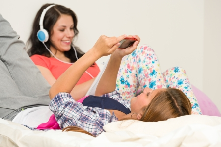 Teen girls relaxing on bed with mobile phone and headphones Stock Photo - 20244486