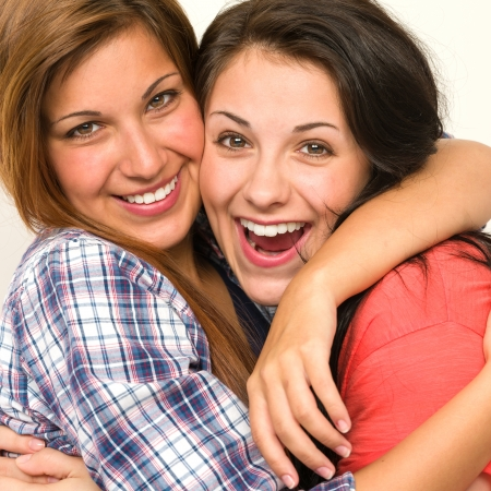 friends hugging: Caucasian sisters friends embracing and  laughing at camera