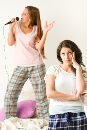 sleepover: Young girl annoyed with her friend singing karaoke Stock Photo