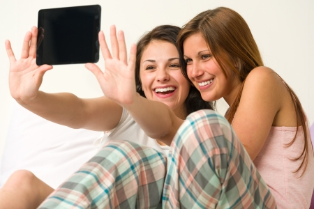 Pretty young girls taking pictures of themselves smiling Stock Photo - 20244512