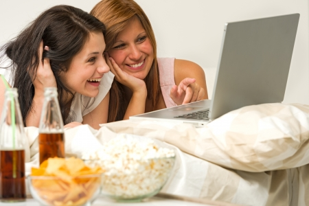 Teenagers friends enjoy movie night watching laptop and laughing photo