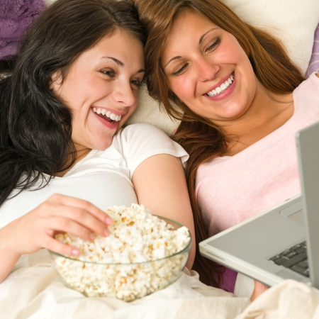 sleepover: Pretty sisters lying on bed watching funny movie