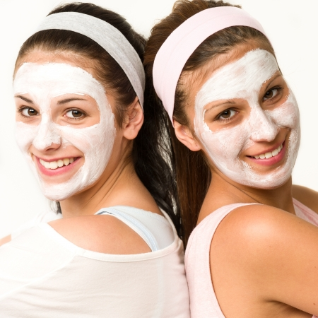 exfoliate: Happy caucasian girls with white facial mask