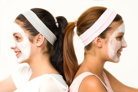 Girls sitting back-to-back wearing white facial mask Stock Photo - 20244526