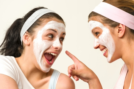 Joyful girls wearing white mask and laughing at each other Stock Photo - 20244518