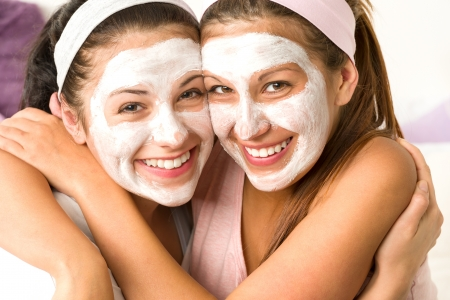 Blissful girls applying white facial mask hugging each other