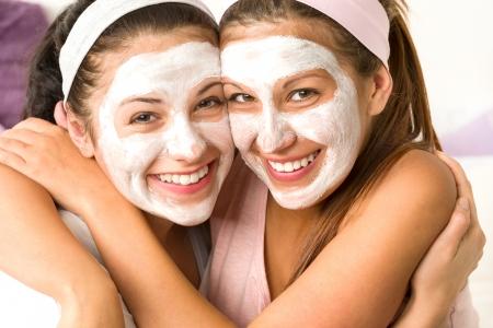Zalige meisjes toepassing van witte gezichtsmasker knuffelen elkaar