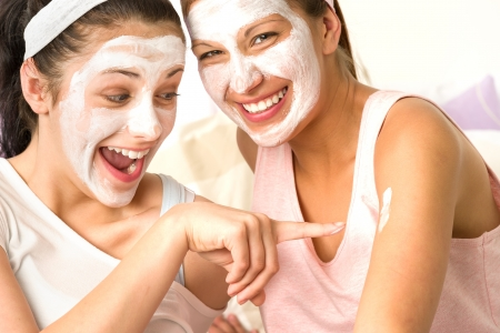 Laughing caucasian girls wearing peeling mask having fun Stock Photo - 20244524
