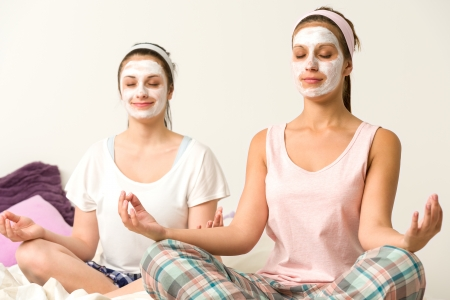exfoliate: Meditating women sitting cross-legged  wearing white facial mask