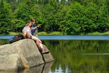 湖のほとりに岩の上に座っている若いハイカー カップル