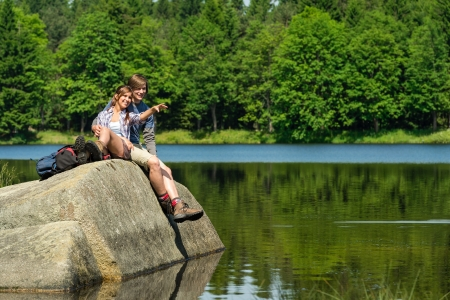 lifestyle outdoors: Young hikers couple sitting on rock by the lake