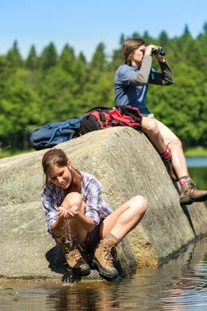 birdwatching: Teenagers resting and birdwatching by lake young hikers sporty Stock Photo
