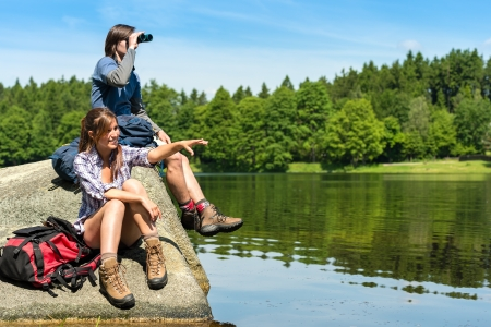 Caucasian teenage hikers birdwatching at lake photo
