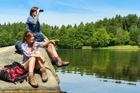 Excursionistas adolescentes caucásicas de observación de aves en el lago