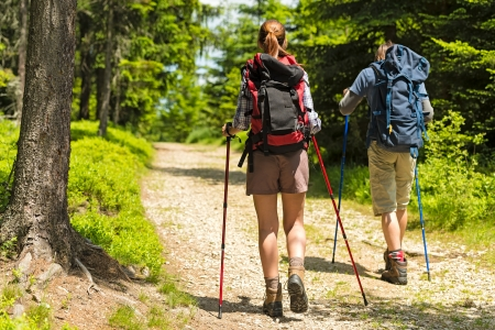 Sporty hikers on path with trekking poles photo
