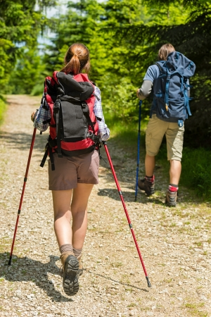 trekking pole: Teen tourists walking with trekking poles in woods Stock Photo
