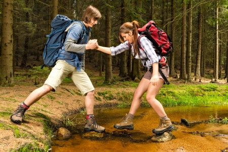 Woods: Hiker boy help trekking girl crossing the creek