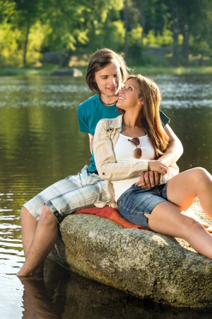 Romantic couple sitting on a rock looking at each other photo
