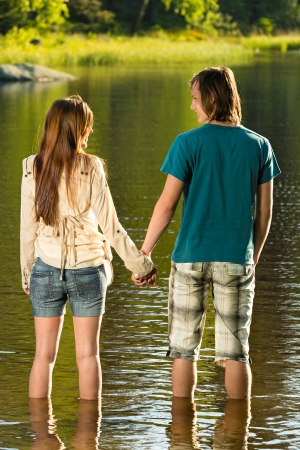Teenage couple holding hands standing in water sunset by lake photo