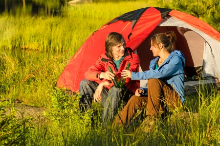 Camping teenagers drink beer outdoors sunset on the meadow photo