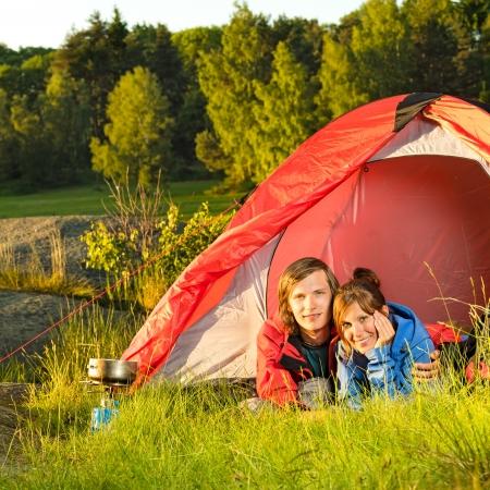 Jong koppel camping omarmen en ligt in de tent Stockfoto