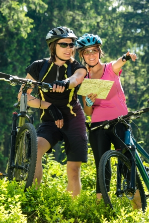 Young cheerful bikers checking the map sunny day in nature