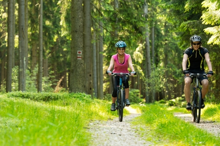 Young cheerful biker couple in woods photo