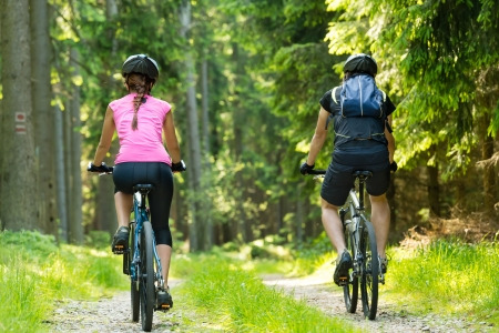 Bikers in forest cycling on track from behind photo