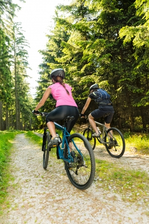 Sporty mountain bikers in forest from behind photo