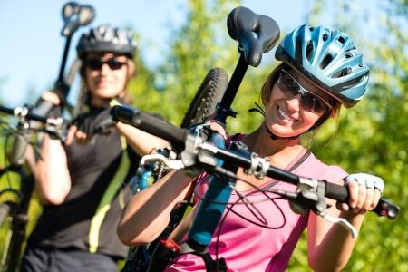 mountain bike: Smiling sporty couple carrying their mountain bikes