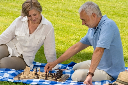 Retired senior couple playing chess in park sitting blanket grass photo