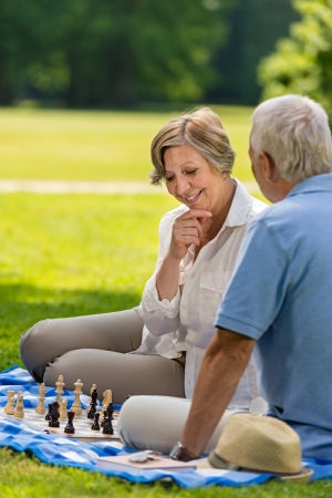 Elderly friends couple playing chess in park on sunny day photo