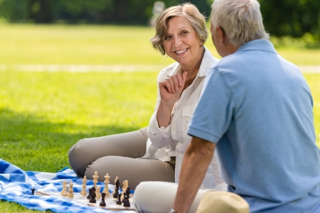 Senior wife and husband playing chess on blanket summer park Stock Photo