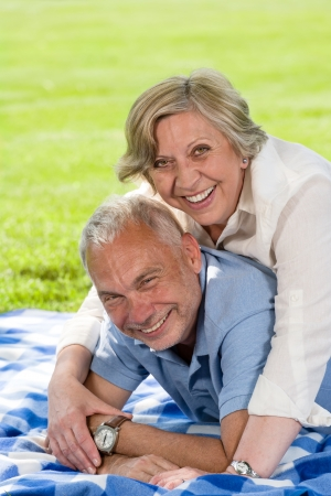 Active retirement laughing senior couple lying in grass photo