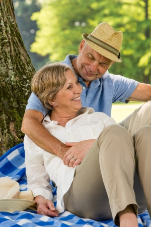 Happy elderly wife and husband hugging in park photo
