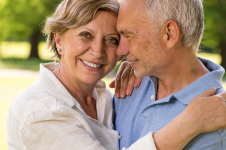 Elderly wife and husband cuddling and smiling outdoors photo