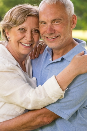 Senior couple hugging and smiling in park looking at camera photo
