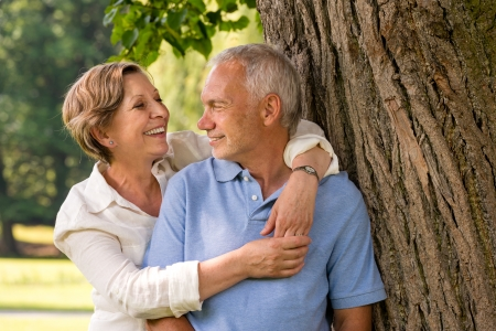 Happy pensioner couple cuddling outdoors leaning against tree Stock Photo - 21302815