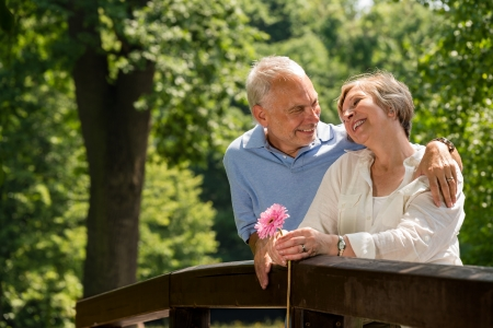 Retired romantic couple hugging and smiling in park photo