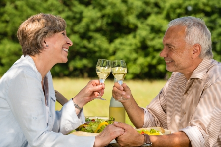 Elderly caucasian couple celebrating outdoors photo