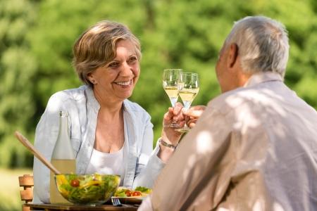 Happy senior citizens clinking glasses in garden Imagens