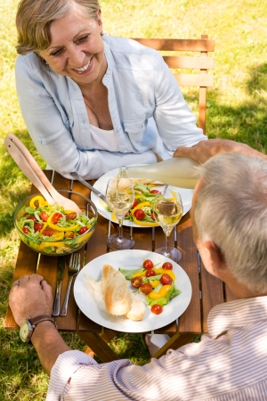 Smiling retired couple eating and drinking outdoors photo