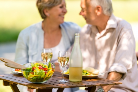 Cheerful senior citizens dating and eating outdoors photo