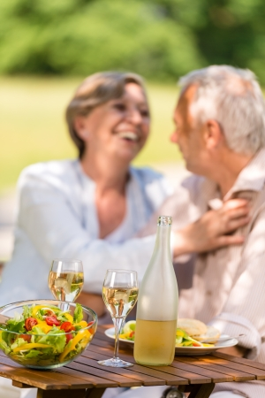 Happy senior wife and husband dining outdoors photo