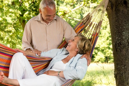 Happy senior couple relax hammock outdoors looking at each other photo