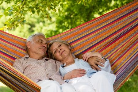 Senior couple relax sleeping together in hammock sunny garden