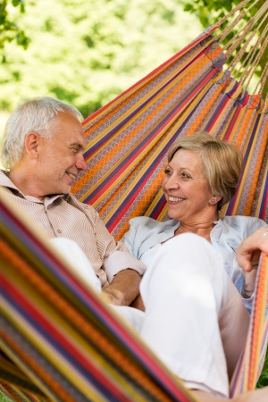 Happy elderly couple lying in hammock photo